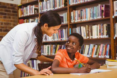 ni�os con l�pices: Retrato del profesor ayudando ni�o con la tarea en la biblioteca