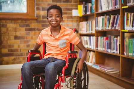 Dzieci: Portret mały chłopiec siedzi w wózku w bibliotece