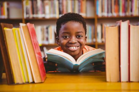 Симпатичный маленький мальчик, чтение книги в библиотеке