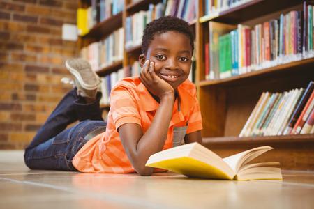 gar�on souriant: Mignon petit livre de lecture gar�on dans la biblioth�que Banque d'images