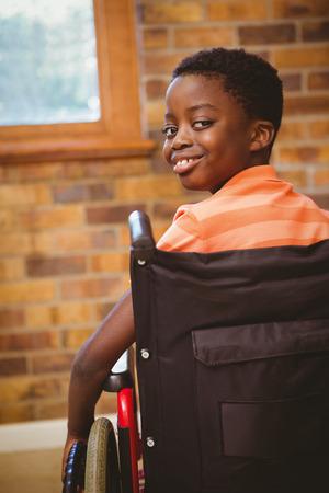 Portrait of cute little boy sitting in wheelchair in school
