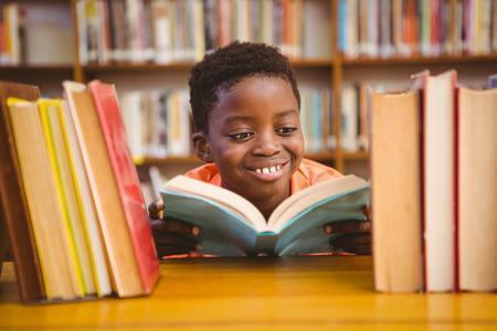 Boek Schattige kleine jongen het lezen in de bibliotheek Stockfoto