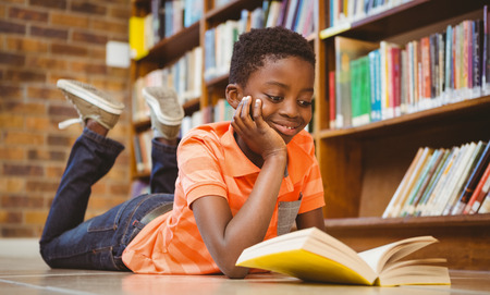 child book: Cute little boy reading book in the library Stock Photo