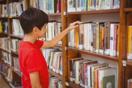 biblioteca: Vista lateral de niño lindo que selecciona el libro en la biblioteca