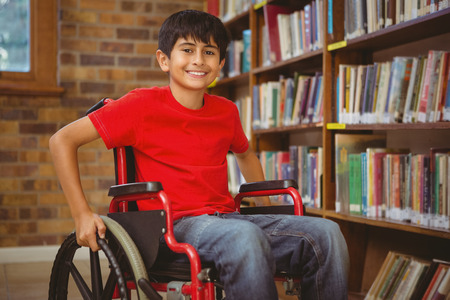 discapacitados: Retrato de niño sentado en silla de ruedas en la biblioteca