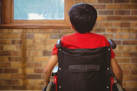 Rear view of little boy sitting in wheelchair in school