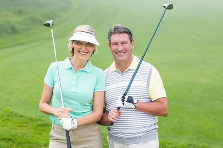 golf glove: Golfing couple smiling at camera holding clubs on a foggy day at the golf course Stock Photo