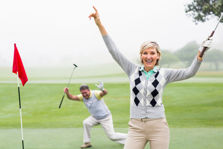woman golf: Lady golfer cheering at camera with partner behind on a foggy day at the golf course