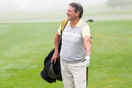 golf bag: Handsome golfer standing with golf bag on a foggy day at the golf course
