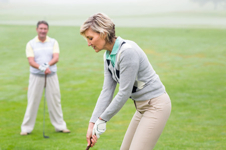 golf swings: Lady golfer teeing off for the day watched by partner on a foggy day at the golf course Stock Photo