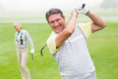 mature female: Happy golfer teeing off with partner behind him on a foggy day at the golf course