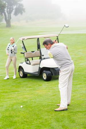 off course: Golfer about to tee off with partner behind him on a foggy day at the golf course