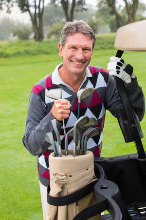 Happy golfer beside his golf buggy on a sunny day at  the golf course photo