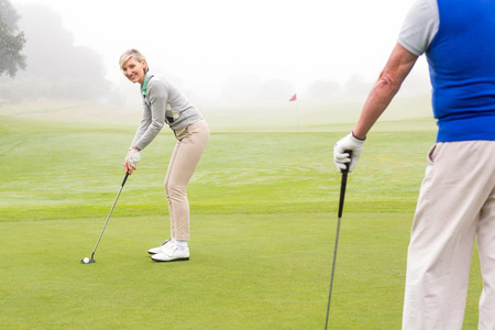 Lady golfer teeing off for the day watched by partner on a foggy day at the golf course photo