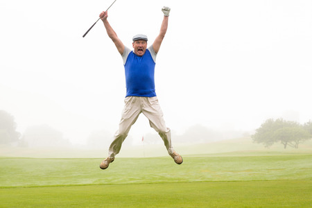 Excited golfer jumping up and smiling at camera on a foggy day at the golf course
