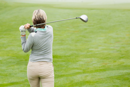recreational pursuits: Lady golfer teeing off for the day on a foggy day at the golf course