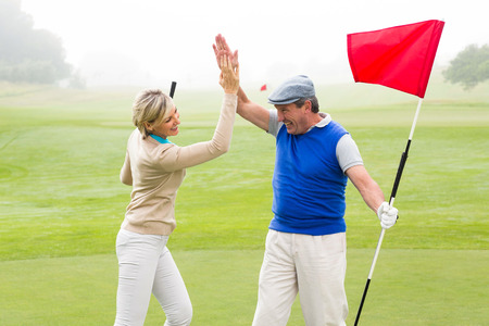Golfing couple high fiving on the golf course on a foggy day at the golf course