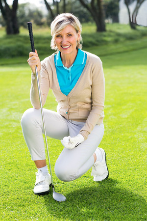 golf cap: Cheerful golfer smiling at camera holding her club on a sunny day at the golf course Stock Photo