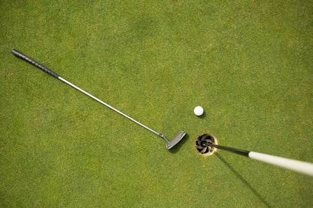pelota de golf: Club de golf y pelota de golf en el putting green junto a la bandera en un d�a soleado Foto de archivo