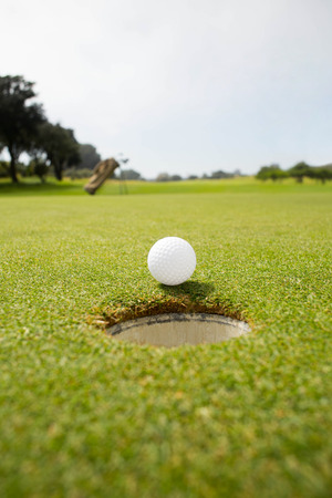 pursuits: Golf ball at the edge of the hole on a sunny day at the golf course
