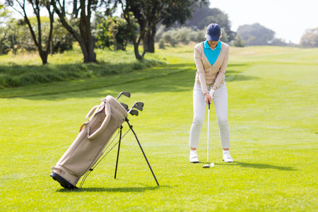 Female concentrating golfer teeing off on a sunny day at the golf course photo