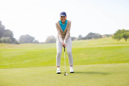 golfer: Female golfer putting her ball on a sunny day at the golf course Stock Photo