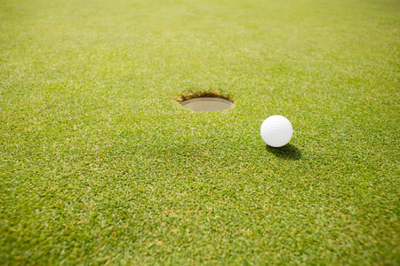recreational pursuits: Golf ball near hole on a sunny day at the golf course Stock Photo