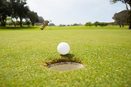 recreational pursuits: Golf ball at the edge of the hole on a sunny day at the golf course