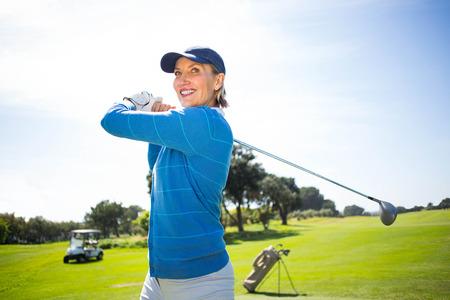 off course: Lady golfer teeing off and smiling on a sunny day at the golf course