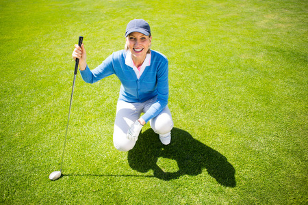 golfer: Smiling lady golfer kneeling on the putting green on a sunny day at the golf course