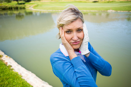 lost lake: Worried female golfer looking for golf ball on a sunny day at the golf course