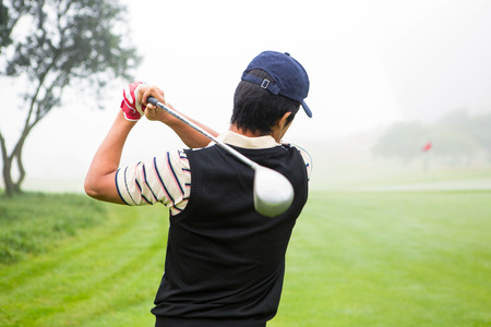 Golfer teeing off at the golf course photo