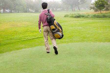golf bag: Golfer walking away holding golf bag at golf course Stock Photo
