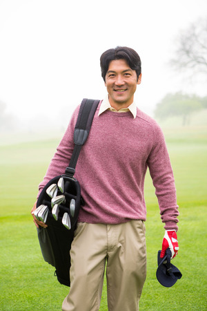 Golfer standing holding his golf bag smiling at camera at the golf course photo