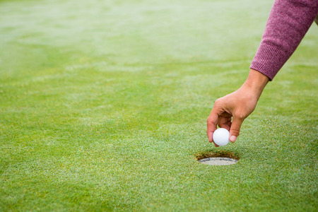 dishonest: Golfer trying to flick ball into hole at the golf course