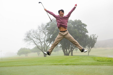 Excited golfer jumping up and smiling at camera at the golf course Stock Photo