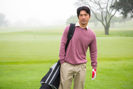 golf bag: Golfer standing holding his golf bag at the golf course