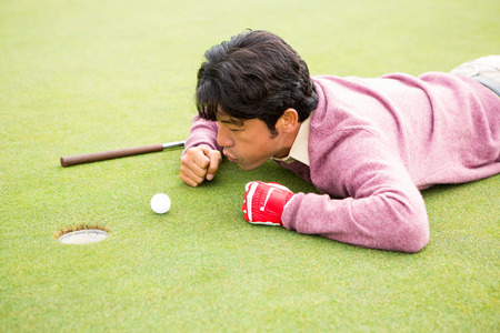 flicking: Golfer trying to flick ball into hole at the golf course