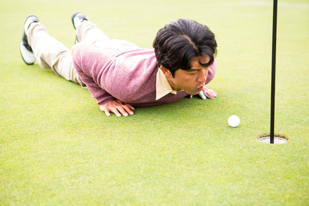flick: Golfer trying to flick ball into hole at the golf course