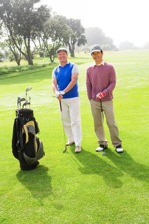 Golfing friends smiling at camera holding clubs at the golf course photo