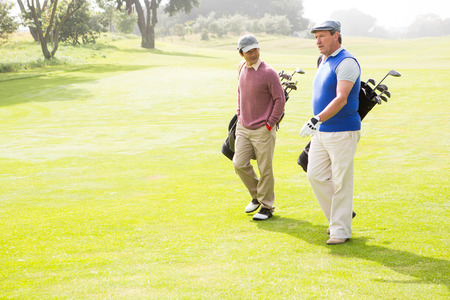 Golfer friends walking and chatting on a sunny day at the golf course photo