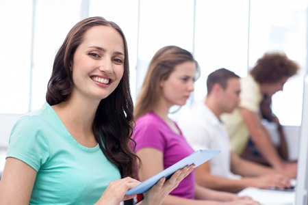 Female student smiling at camera in computer class photo