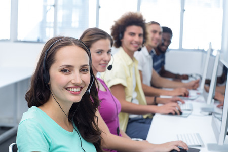 Portrait of smiling students using headsets in computer class photo