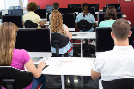 student study: Rear view of students sitting in computer class Stock Photo