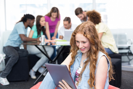 wireless technology: Smiling female student using digital tablet with friends in background