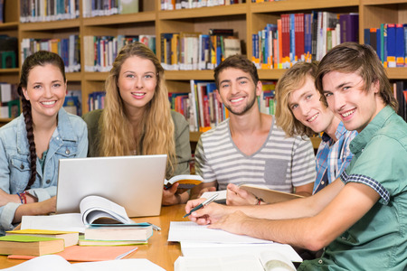 Group of college students doing homework in the library photo