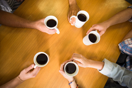 women holding cup: High angle view of hands holding coffee mugs on table Stock Photo