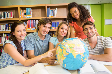 higher intelligence: Group of college students pointing at globe in the library