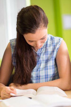 higher intelligence: Portrait of female student reading book in the library