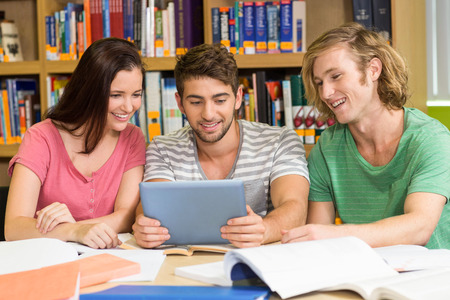 higher intelligence: Group of college students using digital tablet in the library Stock Photo